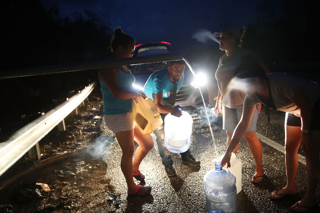 UTUADO, PUERTO RICO - OCTOBER 06:  People collect spring water in containers from a pipe along side a highway since they have no running water in their home after Hurricane Maria passed through on October 6, 2017 in Utuado, Puerto Rico.  Puerto Rico experienced widespread damage including most of the electrical, gas and water grid as well as agriculture after Hurricane Maria, a category 4 hurricane, passed through.  (Photo by Joe Raedle/Getty Images)