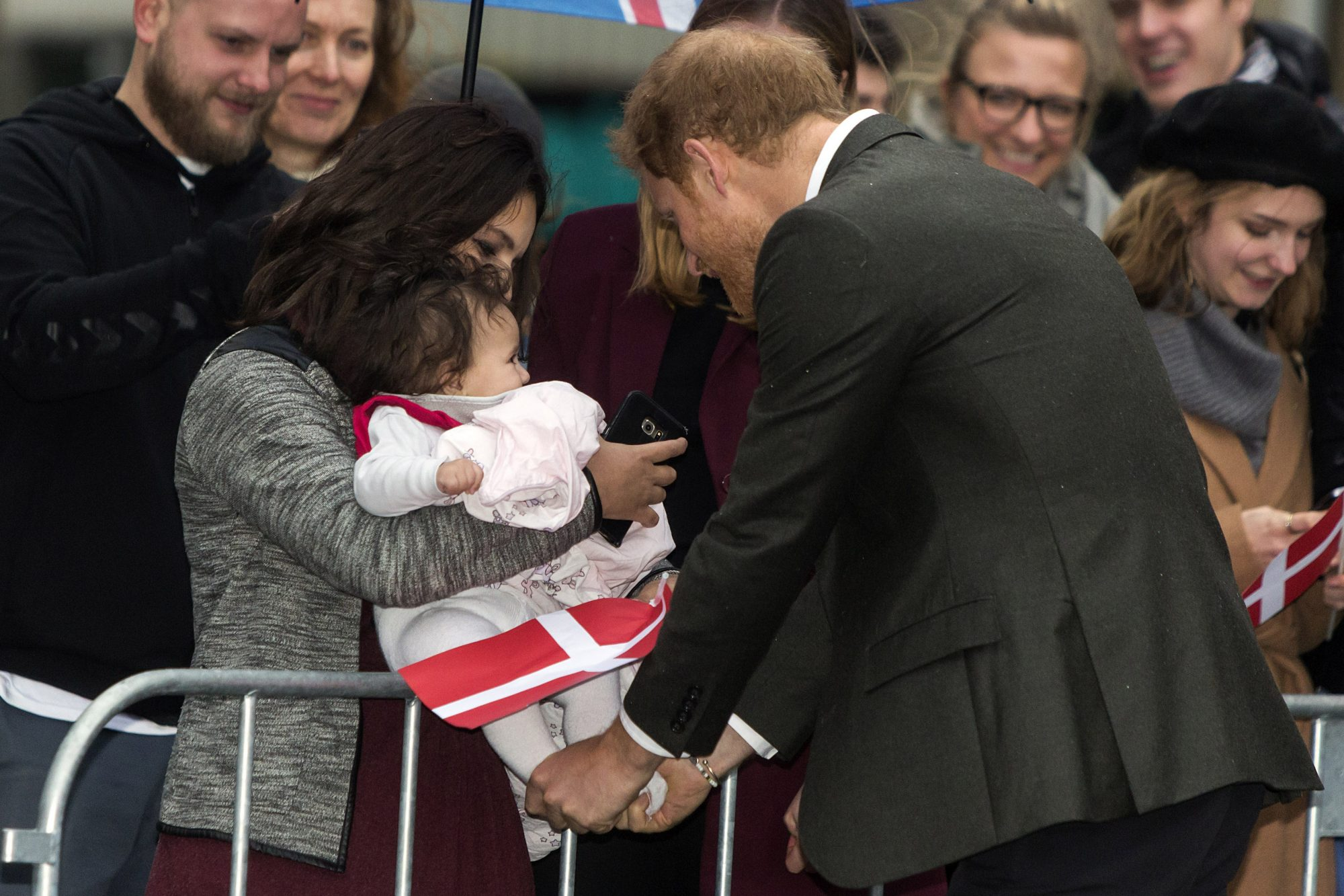 COPENHAGEN, DENMARK - OCTOBER 25:  (EDITOR'S NOTE: Alternative crop of image # 866308774)   Prince Harry holds the feet of a baby as he greets the public on arrival for Game Denmark during the first of his two days stay in Denmark on October 25, 2017 in Copenhagen, Denmark. At the photo the Prince holds the little baby's feeds -  maybe be course it was a cold and wet day. Game Denmark is a street sport activity center for youngsters. (Photo by Ole Jensen - Corbis/Corbis via Getty Images )