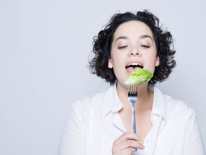 Woman eating lettuce off fork