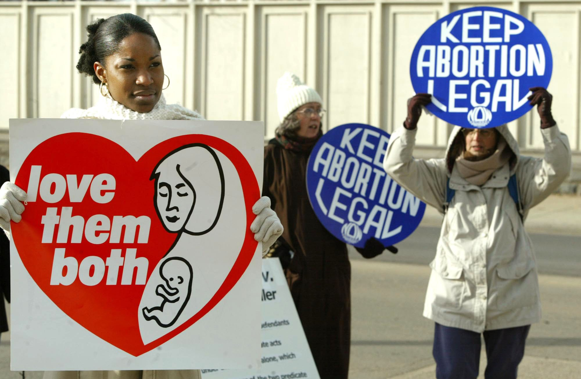 WASHINGTON - DECEMBER 4: Tiffany Keeler (L) holds a sign reading 'Love them both' as people hold 'Keep Abortion Legal' signs during a protest in front of the U.S. Supreme Court December 4, 2002 in Washington, DC. The high court is hearing oral arguments in the Scheidler v. NOW case and is considering whether the RICO act can be used to punish anti-abortion protesters. Operation Rescue, anti-abortion leader Joseph Scheidler and others are appealing a case first dealt with nine years ago to the Supreme Court. The National Organization for Women (NOW) and abortion clinics in Wisconsin and Delaware sued the anti-abortion groups for 'violent tactics.' (Photo by Mark Wilson/Getty Images)