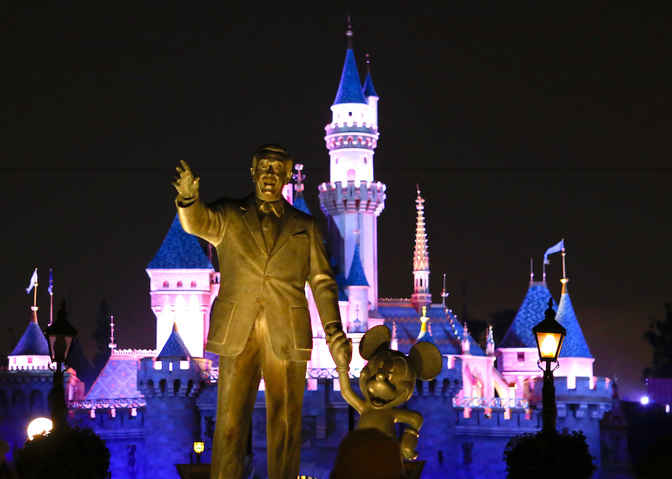 A statue of Walt Disney and Mickey Mouse in front of the Sleeping Beauty Castle at Disneyland Park in Anaheim, California