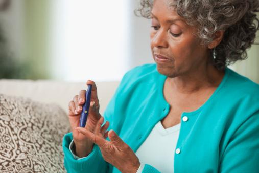 Black woman using diabetes test kit