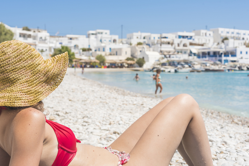 Young woman sunbathing on the beach, wearing a sun hat and a red bikini