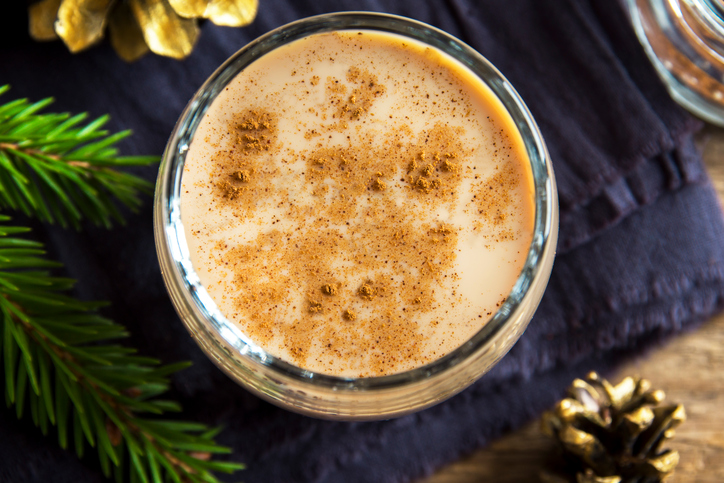 Eggnog with cinnamon in glass close up with Christmas decor - homemade traditional festive drink for Christmas time