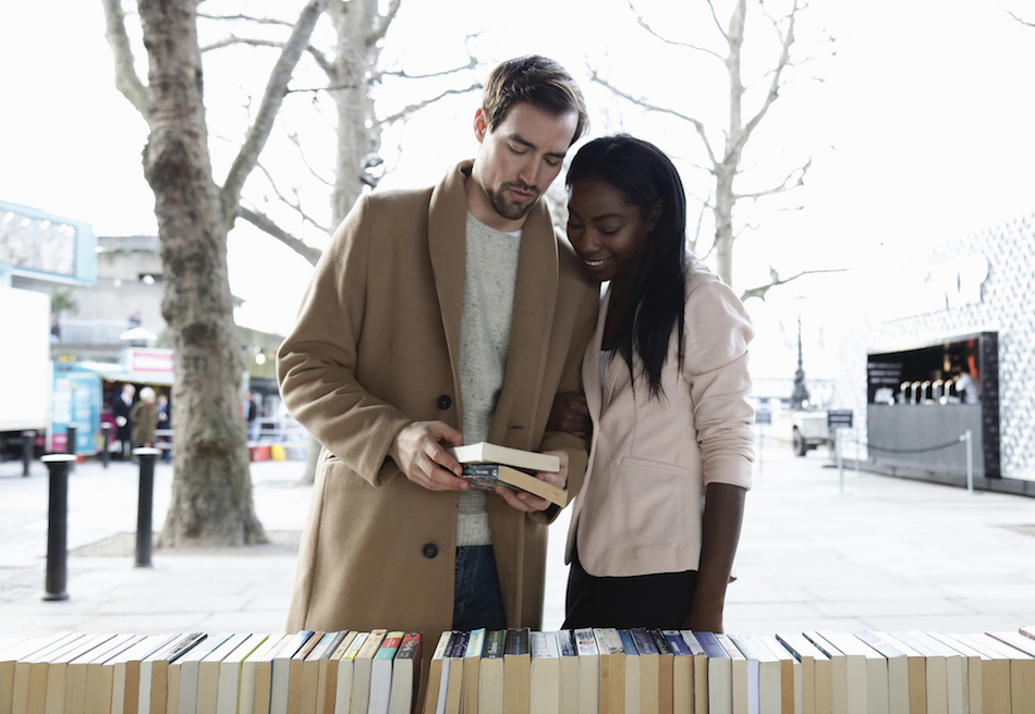 Couple looking at books on market stall