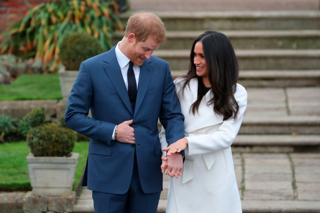 Britain's Prince Harry stands with his fiancée US actress Meghan Markle as she shows off her engagement ring whilst they pose for a photograph in the Sunken Garden at Kensington Palace in west London on November 27, 2017, following the announcement of their engagement.