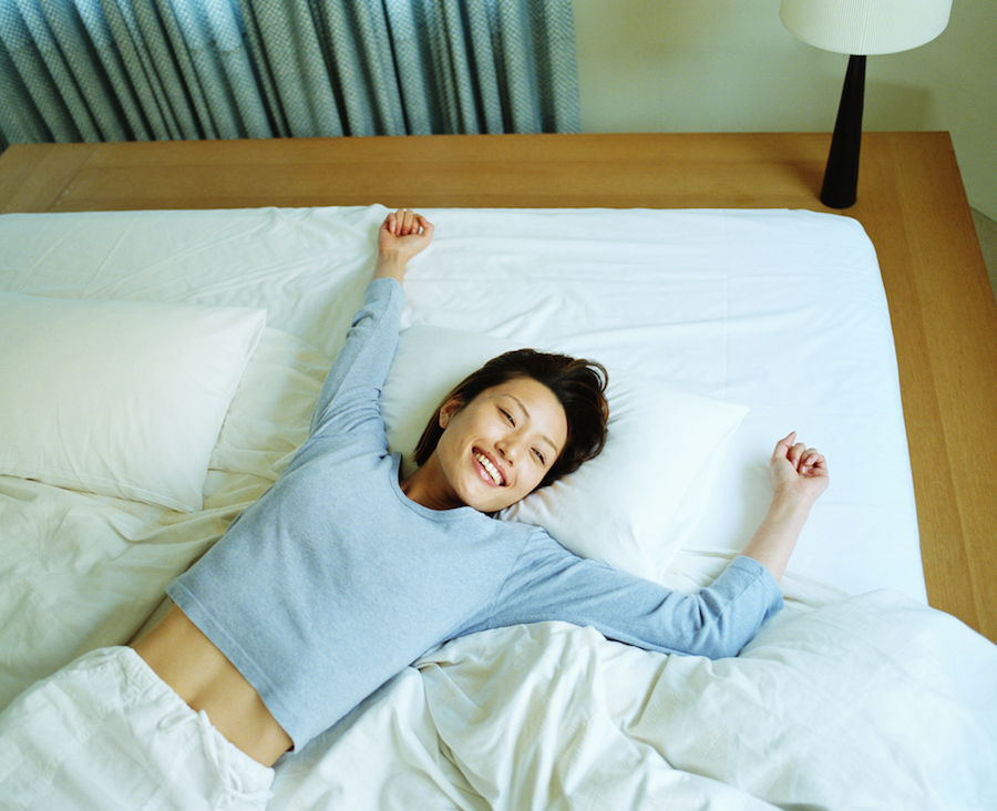 Young woman lying on bed, smiling, elevated view
