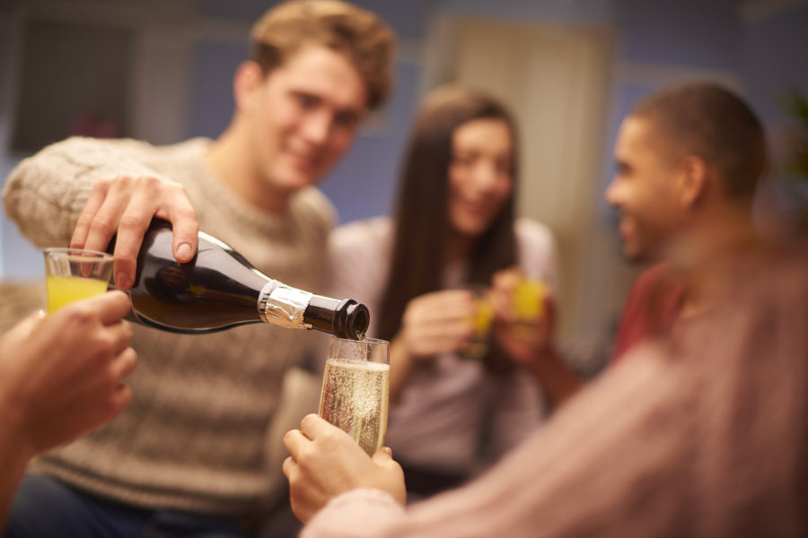 a group of young friends sit on the sofa and share drinks, chatting and laughing with each other .One young man is pouring a glass of prosecco for his friend.