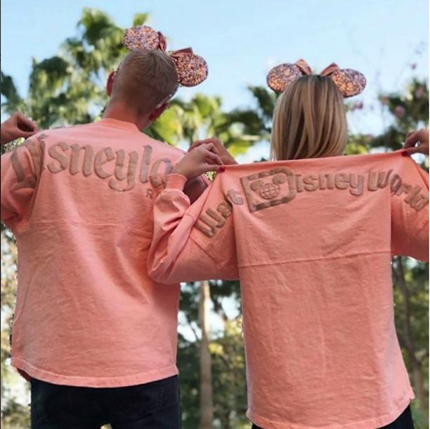 Couple wearing matching rose gold spirit jerseys at Disneyland