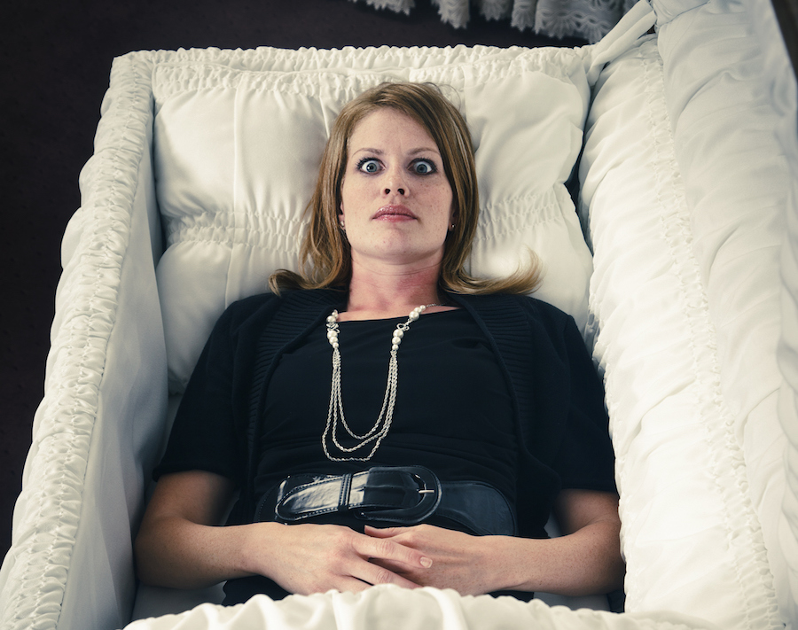 A woman laying in a casket with her eyes wide open.