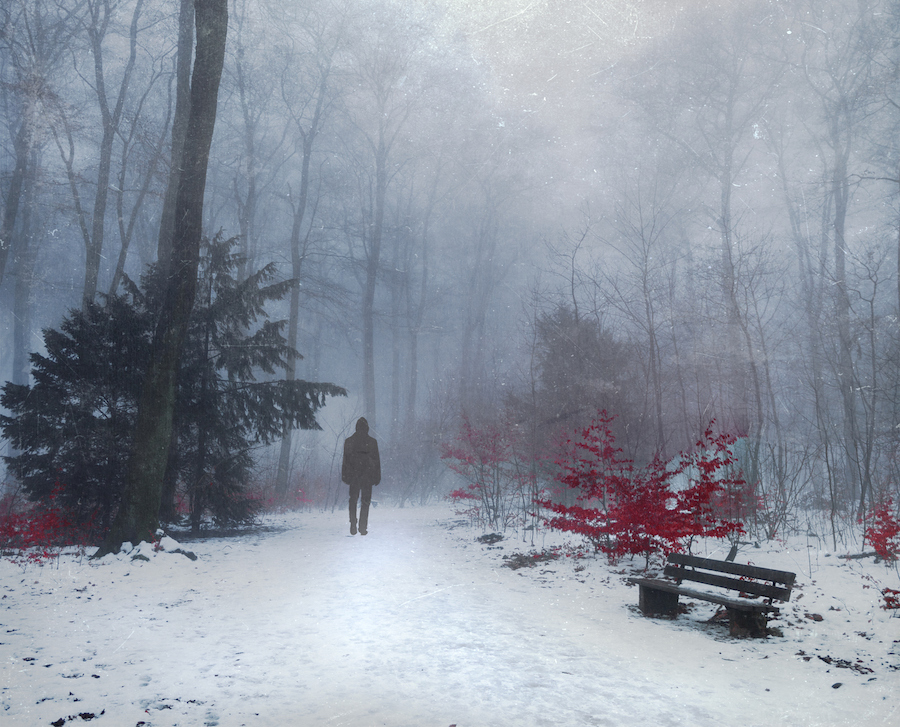 Man walking in snow covered forest, digital alteration