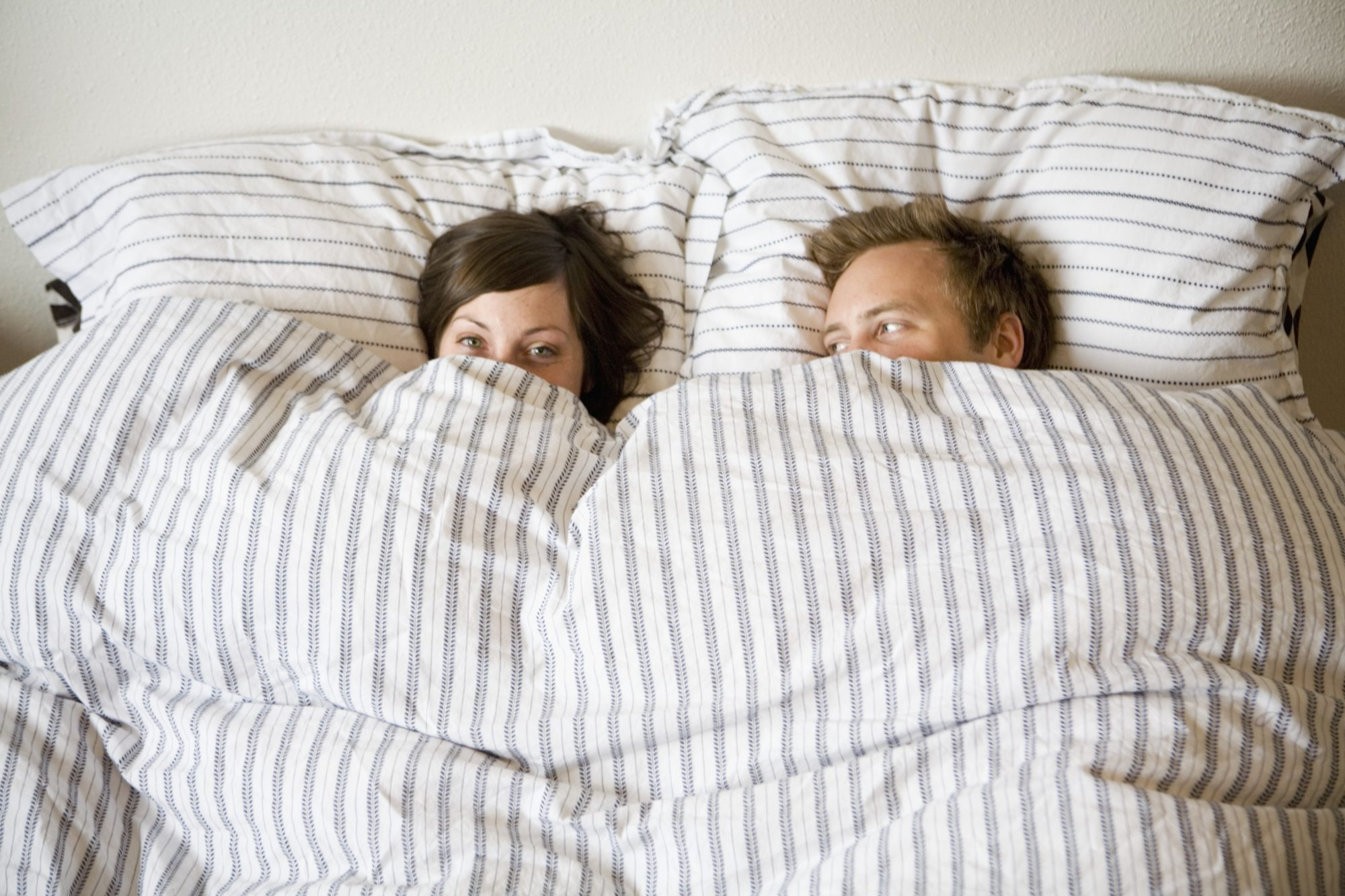 Photo of Couple Cuddling Under the Blankets