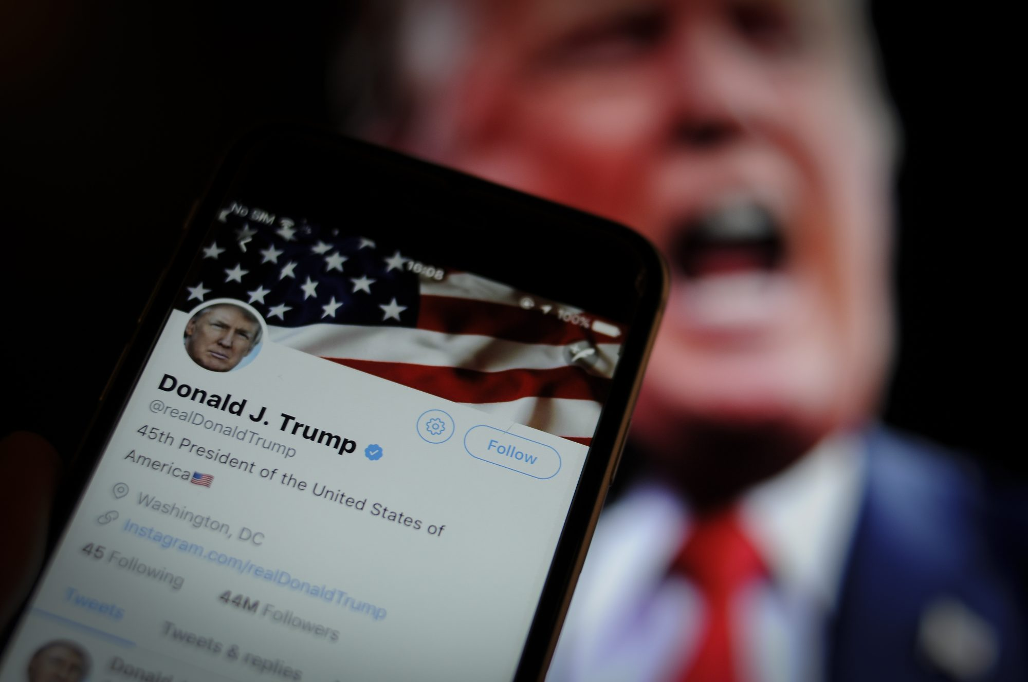 Photo of Twitter App with Donald Trump in the Background