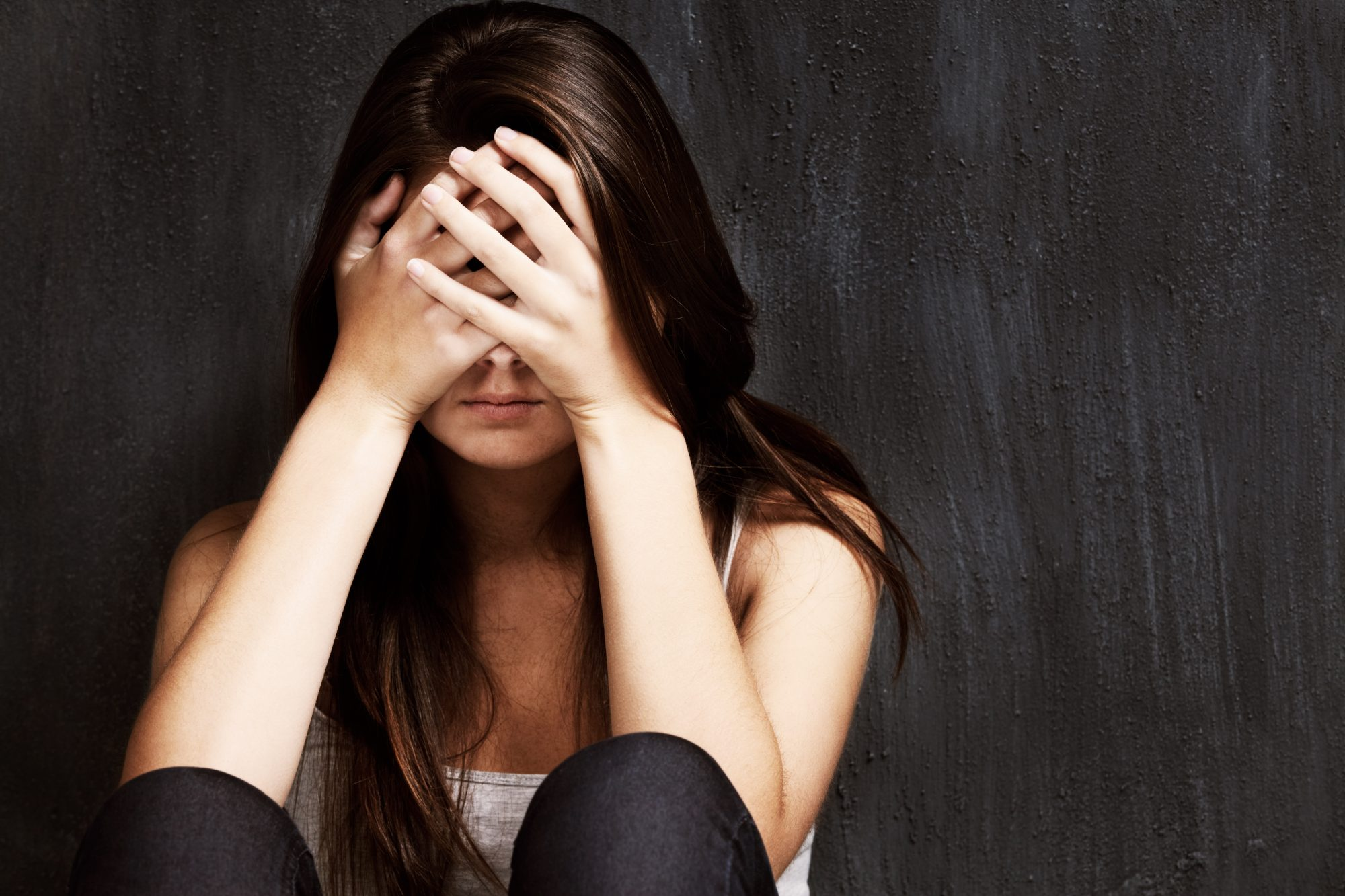 Photo of Sad Young Woman Holding Her Head in Her Hands