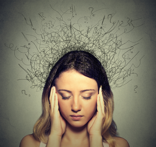 Young woman with stressed expression and question marks around her head