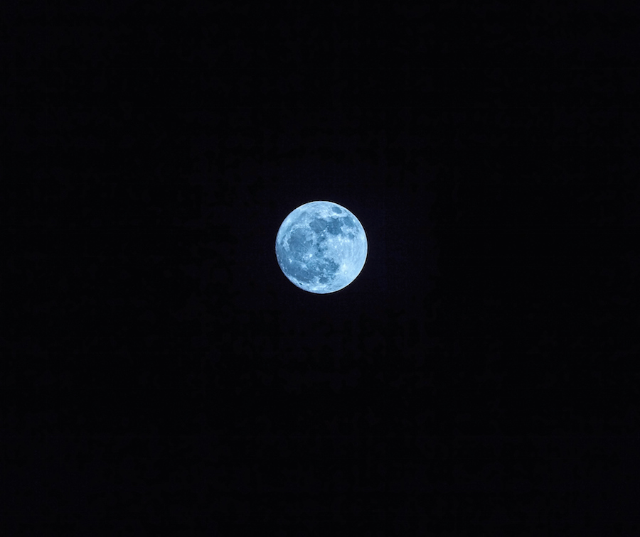 Blue moon in dark sky and far from earth