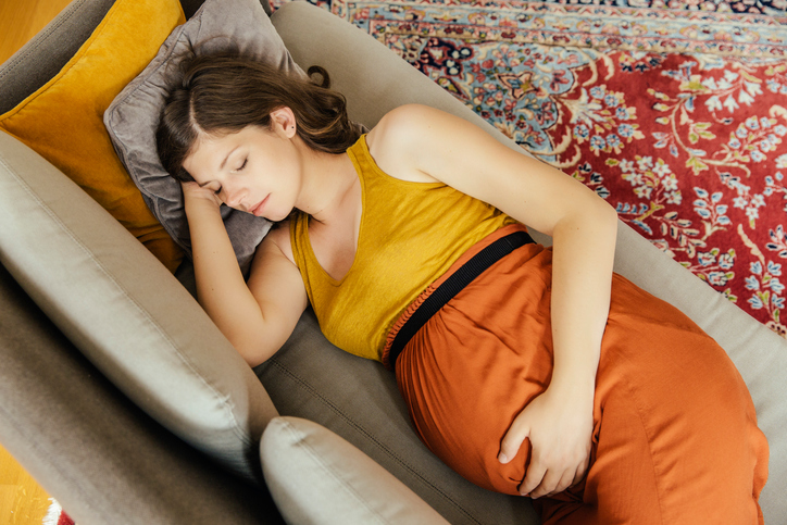 Pregnant woman taking a nap on her couch at home