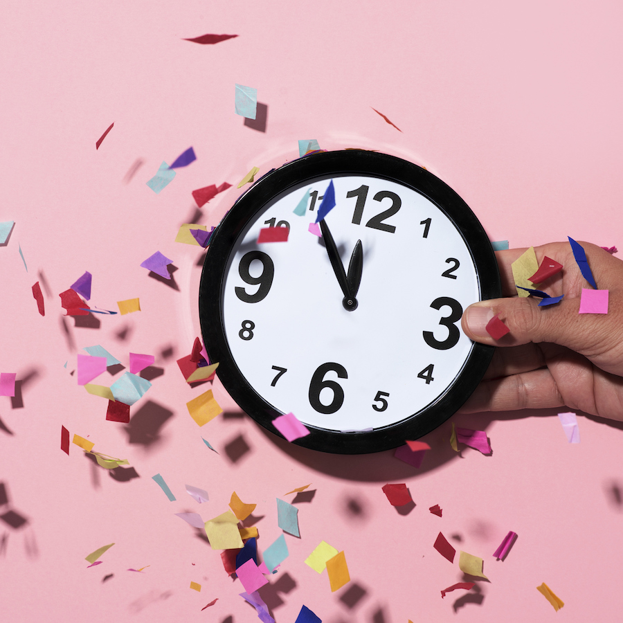 confetti of different colors falling over a clock