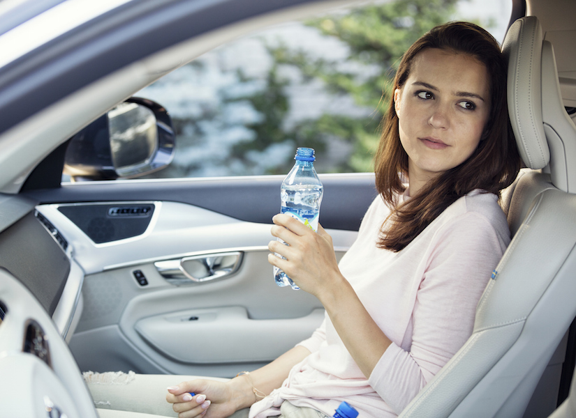 Woman sitting in car, holding bottle of water