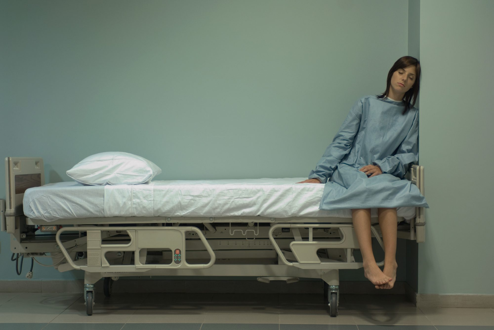 Female patient sitting on hospital bed with eyes closed, leaning head against wall