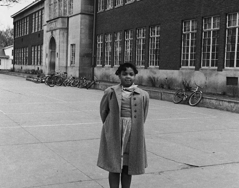 Linda Brown in front of segregated Monroe Elementary School which she attends.