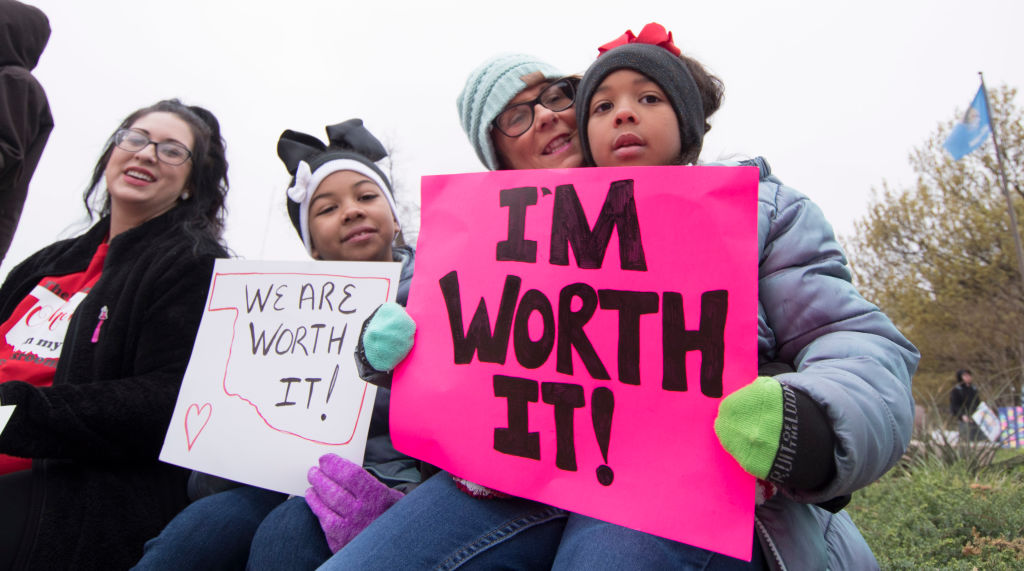 OKLAHOMA CITY, OK - APRIL 2: Natalie Armstrong (left) and her two daughters Payton and Pazyzlrn, along with her mother rally at the state capitol in Oklahoma City, Oklahoma on April 2, 2018. Thousands of teachers and supporters are scheduled to rally Monday at the state Capitol as Oklahoma becomes the latest state to be plagued by teacher strife. Armstrong said she has spent $3,000 this year for school supplies Teachers are walking off the job after a $6,100 pay raise was rushed through the Legislature and signed into law by Gov. Mary Fallin. (Photo by J Pat Carter/Getty Images)