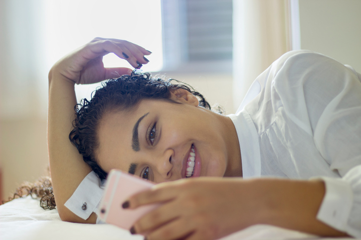 Happy woman sitting on bed reading text message on smartphone. Smiling girl sitting in bedroom in casual in conversation with friend in a chat room.