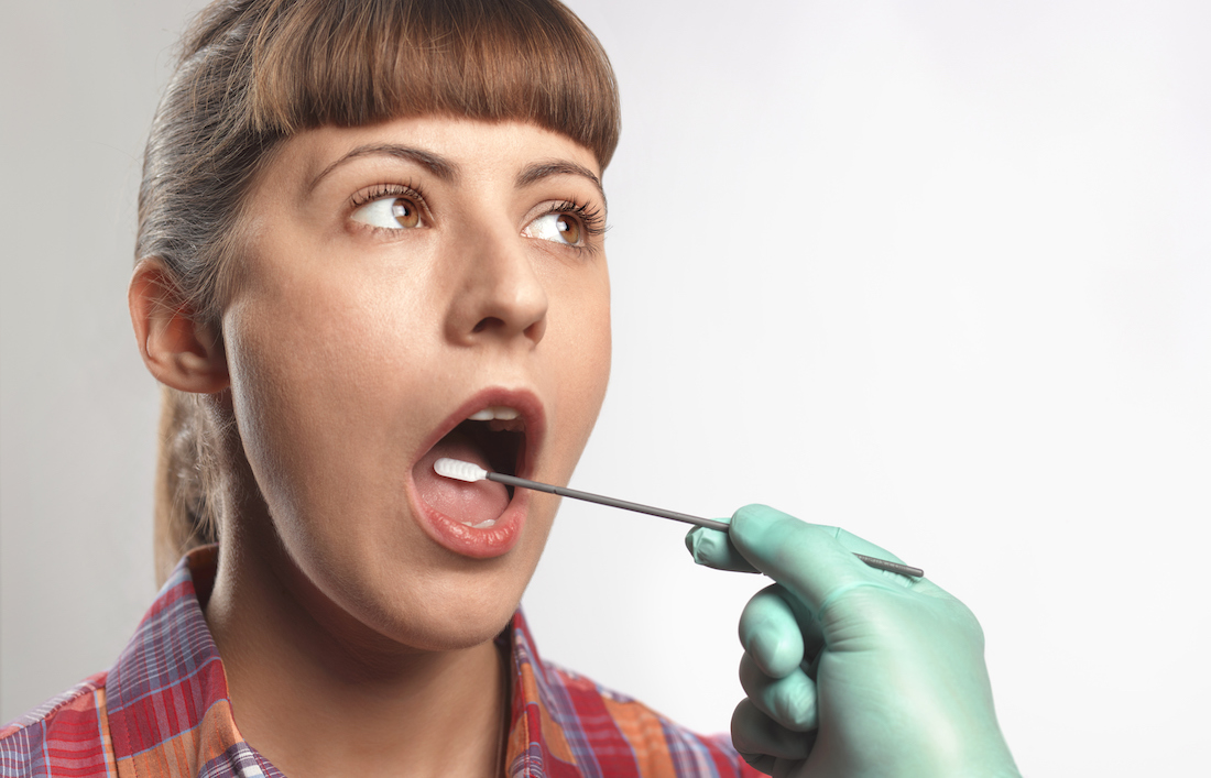 Person putting DNA test swab into woman's mouth