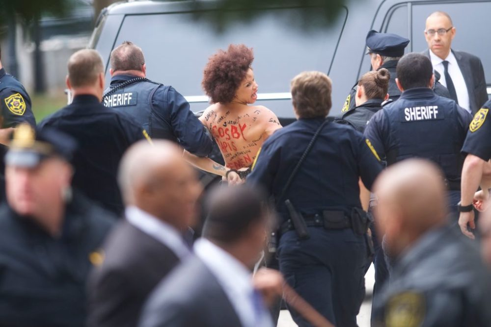 A topless protester lunged at Bill Cosby outside the courthouse where he faces a retrial.