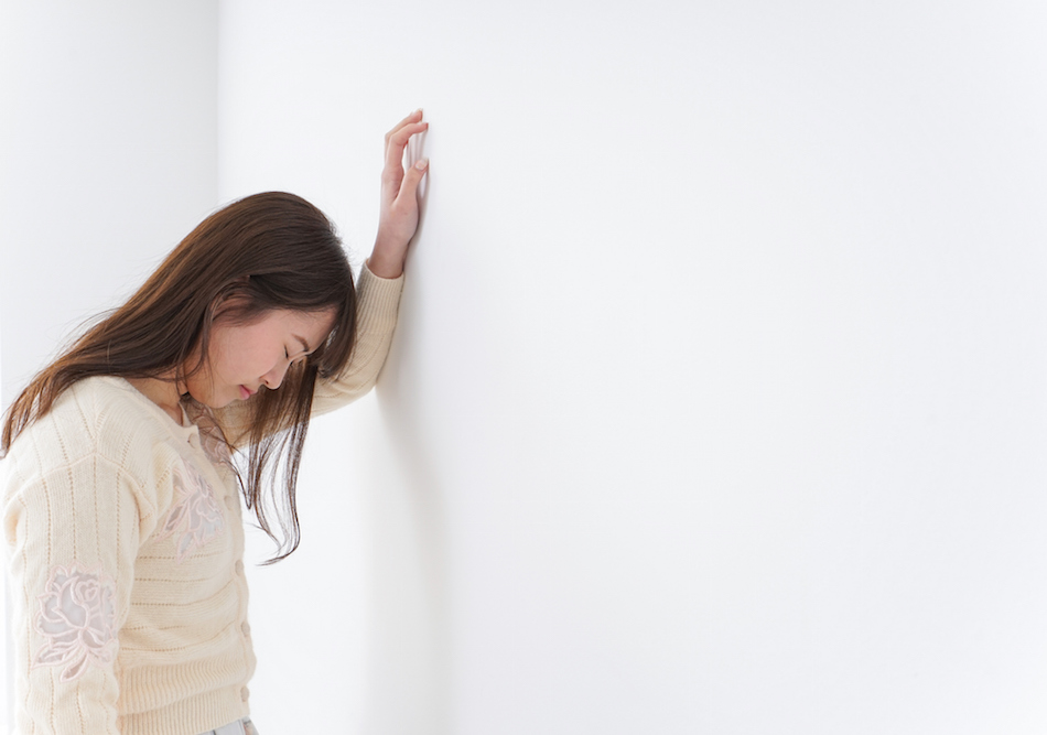 Young woman leaning against wall suffering from illness