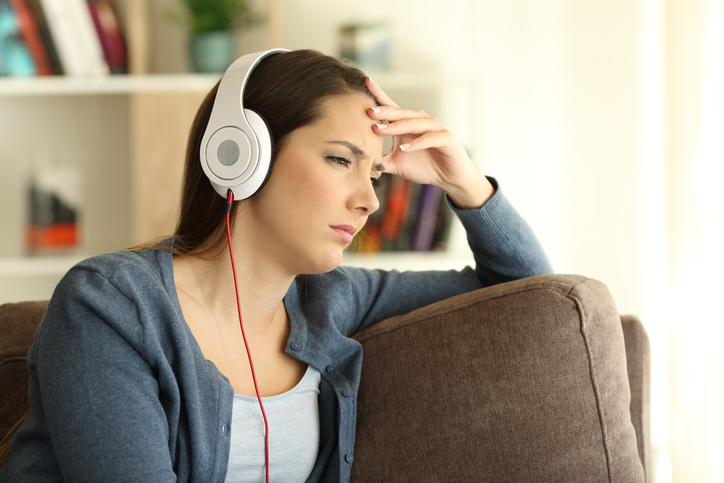 Worried girl listening to music sitting on a couch in the living room at home