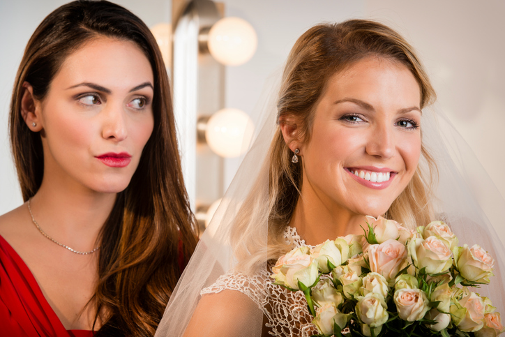 Suspicious bridesmaid standing behind smiling bride