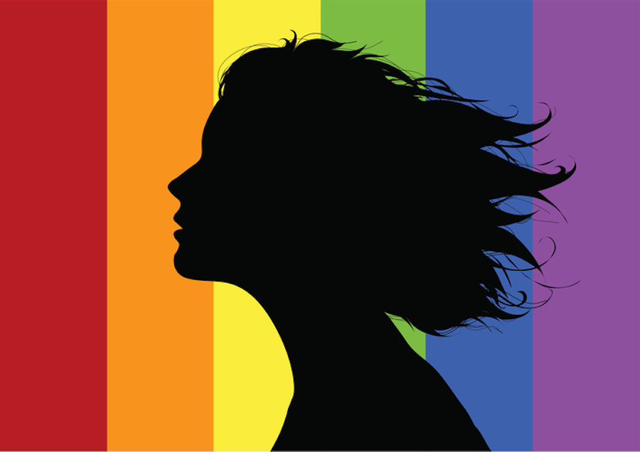 Woman's profile in front of a rainbow flag