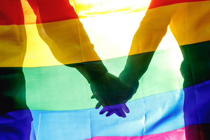 Two people holding hands near Pride flag