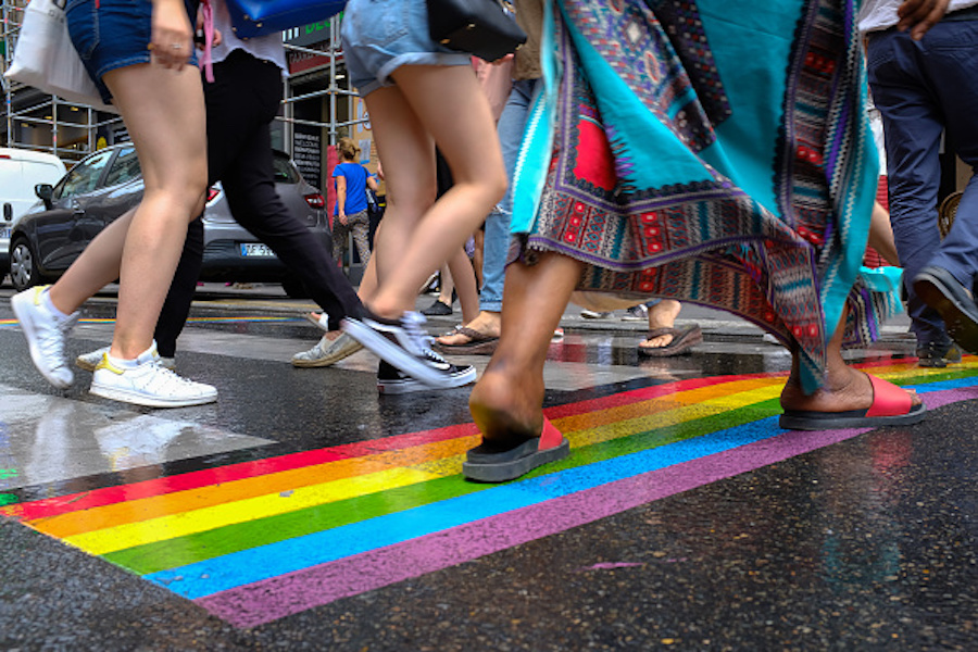 Pedestrians crossing the street at a Pride parade