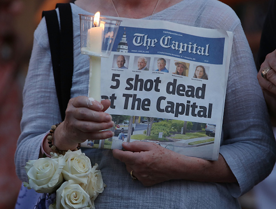 Woman holding up a newspaper at Capital Gazette shooting vigil