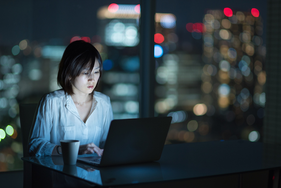Businesswoman working late in office with city in background
