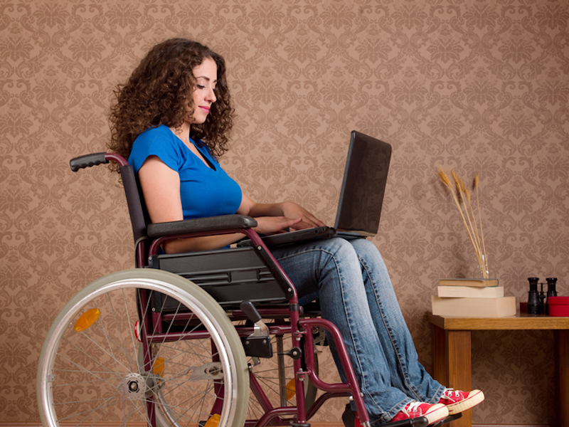 Disabled young woman sitting in wheelchair using laptop