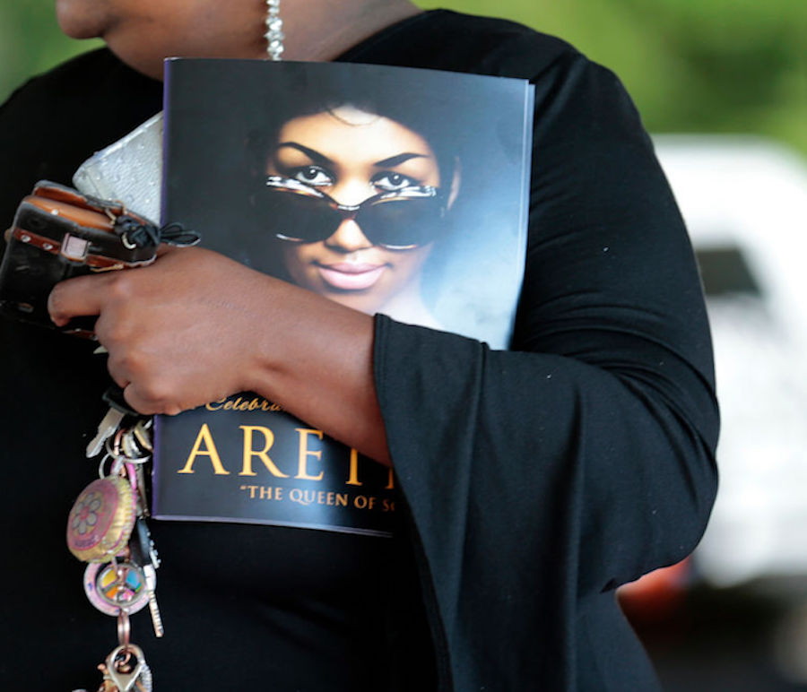 A woman holds a program from Aretha Franklin's funeral