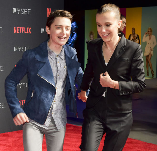 "LOS ANGELES, CA - MAY 19: Actress Millie Bobby Brown (R) and Noah Schnapp arrive at the #NETFLIXFYSEE event for ""Stranger Things"" at Netflix FYSEE at Raleigh Studios on May 19, 2018 in Los Angeles, California."