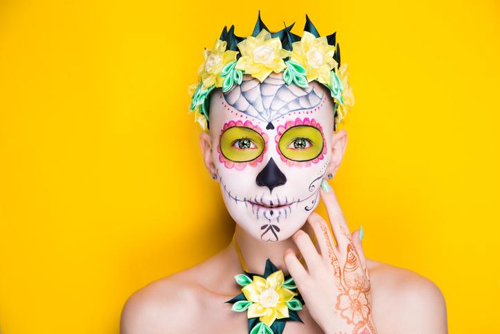 Woman wearing sugar skull makeup for Dia De Los Muertos