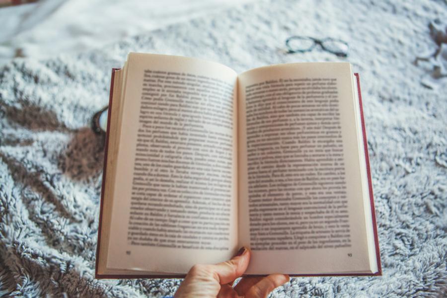 Women's hand holding open book