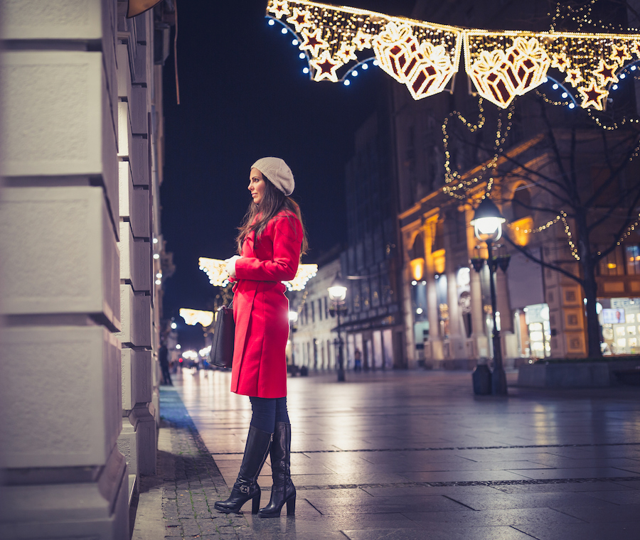 Woman on a street decorated for Christmas