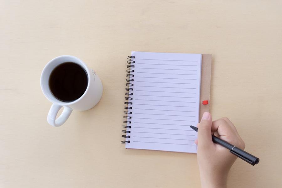 Person writing list next to coffee mug