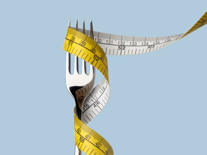 Fork with tape measure on blue background