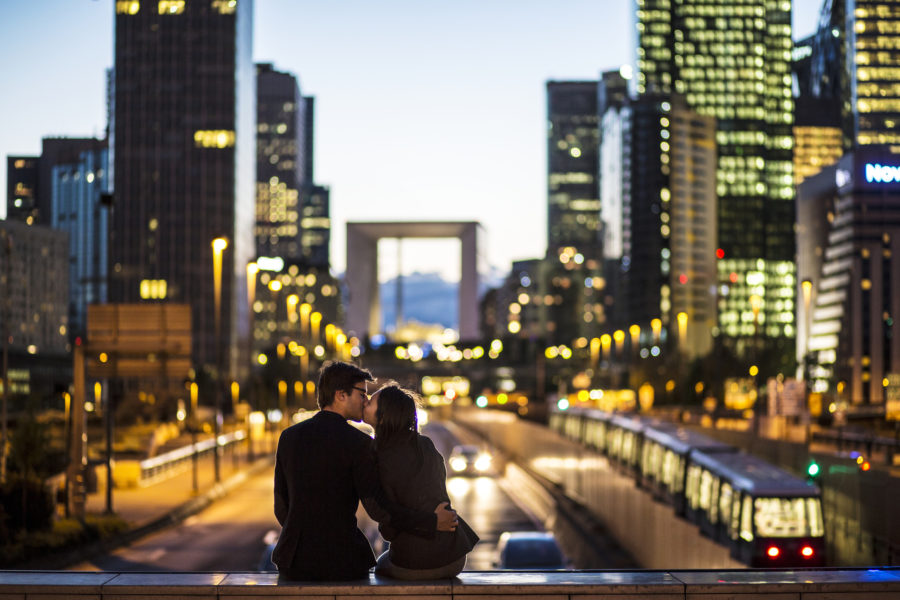 couple kissing in front of bustling city