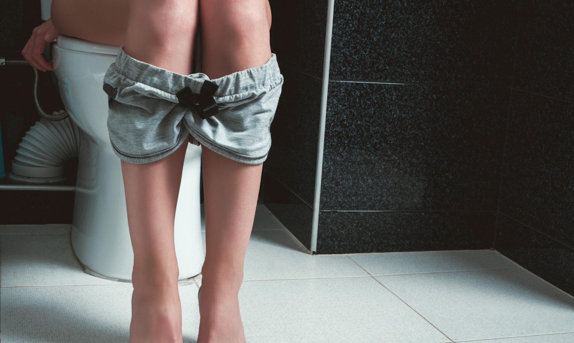 woman sitting on toilet
