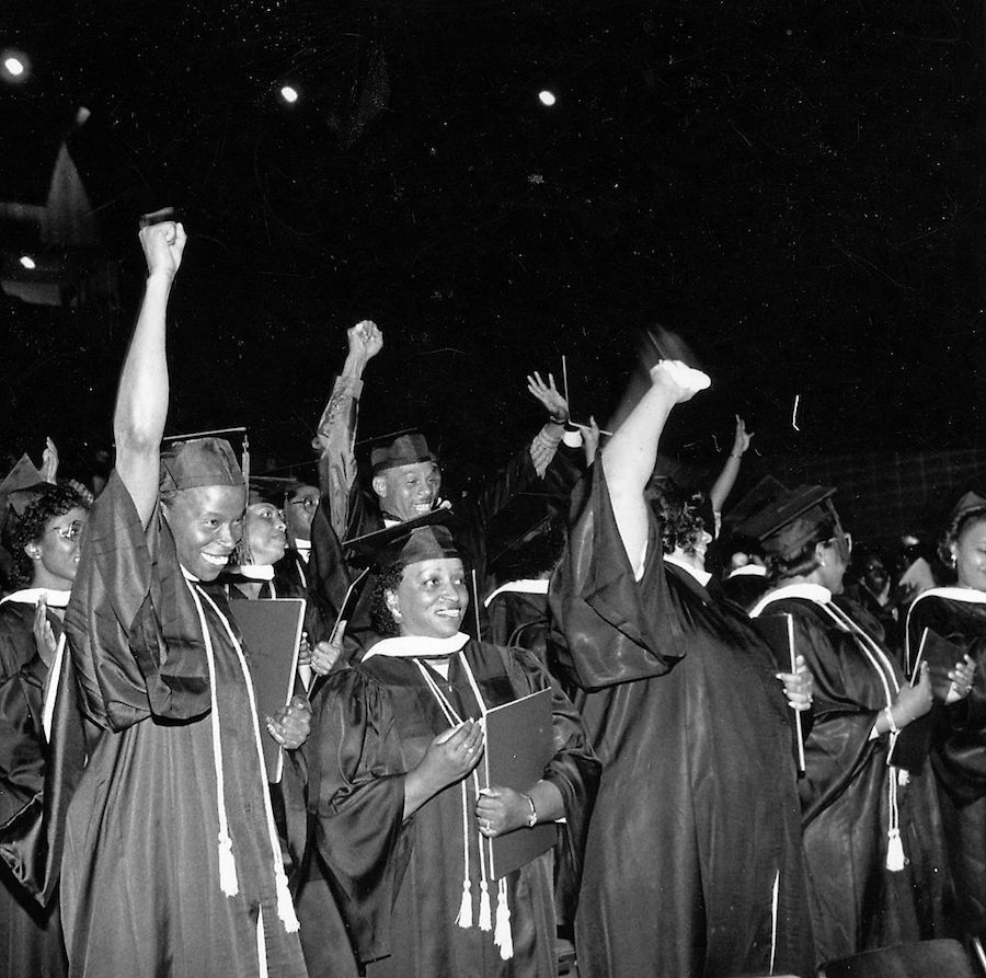 Black students giving the Black Power salute at a college graduation