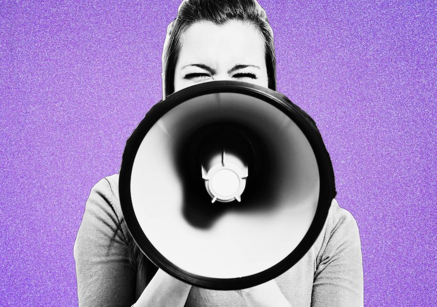 Woman holding megaphone on purple bakground
