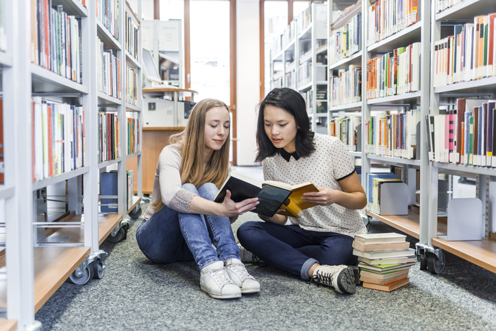 Two young women reading books together